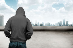 Faceless man in hood. With cityscape background stock photo