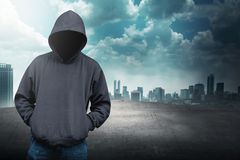 Faceless man in hood on the rooftop. With city background stock image