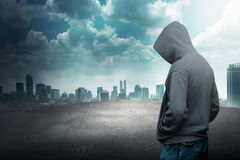 Faceless man in hood on the rooftop. With city background royalty free stock photography