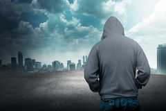 Faceless man in hood on the rooftop. With city background stock images