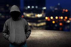 Faceless man in hood on the rooftop. With city background at night time stock photo