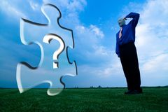 Faceless Man Standing in Field. With his hand up to his head. A puzzle piece with a question mark is superimposed over image stock image