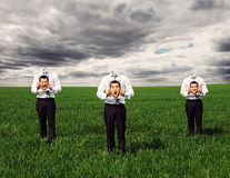 Faceless men standing on the green field Stock Photography