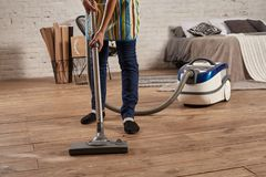 Faceless middle section of young woman using vacuum cleaner in home living room floor, doing cleaning duties and chores. Meticulous interior. Young female stock photos