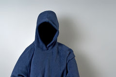 Faceless Person in Blue Hoodie. A blue hoodie with nothing but a dark shadow in place of a face against a white wall with copy-space stock photo