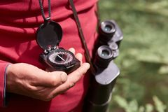 Faceless photo of man`s hand with compass, traveler on wooden background wearing red casual shirt, posing with binoculars, findin. G right way. Traveling royalty free stock photo