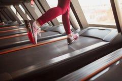 Crop sportswoman running on treadmill stock photo