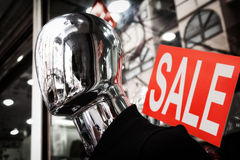 Faceless silver mannequin head close-up. Red sale sign. Faceless silver mannequin head dark close-up. Red sale sign Stock Photos
