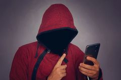Silhouette of a man in a hood on a black background, his face is not visible, the hacker is holding the phone in his hands. The co royalty free stock image