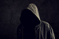 Faceless unrecognizable man without identity. Faceless unknown and unrecognizable man without identity wearing hood in dark room, spooky criminal person Royalty Free Stock Image