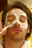 Facemask. A man receives a facial treatment in the spa Royalty Free Stock Image