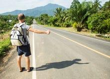 Facendo auto-stop il viaggiatore provi a fermare l'automobile sulla strada della montagna Immagine Stock