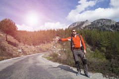 Facendo auto-stop il viaggiatore provi a fermare l'automobile sulla strada della montagna Fotografia Stock