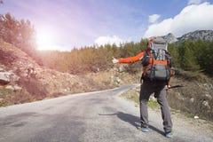 Facendo auto-stop il viaggiatore provi a fermare l'automobile sulla strada della montagna Fotografie Stock Libere da Diritti