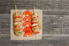 Facendo i kebab dal pollo - carne cruda sugli spiedi sul piatto su fondo di legno invecchiato Fuoco selettivo Stile rustico Posto immagini stock libere da diritti