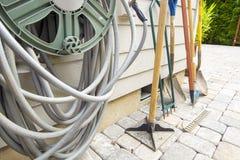 Facendo il giardinaggio e modific il terrenoare gli strumenti innaffiando tubo flessibile fotografie stock