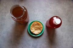 Facendo kombucha a casa: fatto, in bottiglia e una madre su un piatto Fotografia Stock