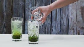 Facendo la soda del tè verde dallo sciroppo del tè verde e dal selz concentrati stock footage