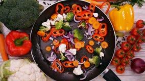 Facendo mescoli le verdure fritte, ingredienti cadono nella padella stock footage