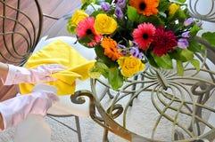 Facendo piazza pulita, spruzzo ed asciugamano vicino ai fiori sulla tavola Fotografia Stock Libera da Diritti