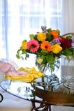 Facendo piazza pulita, spruzzo ed asciugamano vicino ai fiori sulla tavola Immagine Stock Libera da Diritti