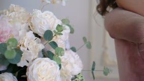 Facendo scorrere macchina fotografica dai fiori ad una donna incinta che tiene un coniglio Fine in su stock footage