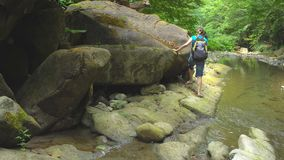 Facendo un'escursione bella donna con lo zaino che si muove lungo la banca pietrosa del fiume della montagna, tenente sopra verso archivi video