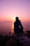 Facendo un'escursione la donna sieda alla spiaggia dell'alba Fotografie Stock