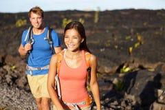 Facendo un'escursione la gente - coppia la camminata sul giacimento di lava Fotografia Stock Libera da Diritti