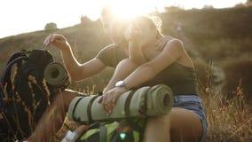 Facendo un'escursione le coppie - viandanti che riposano su una collina Viandante dell'uomo e della giovane donna che si siede su video d archivio