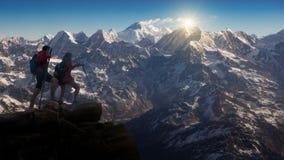 Facendo un'escursione in montagne dell'Himalaya, viandanti con gli zainhi che si rilassano sopra una montagna e che godono della  fotografia stock libera da diritti