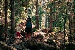 Facendo un'escursione nel legno La madre e la figlia stanno camminando su un percorso fotografie stock libere da diritti
