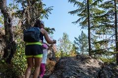 Facendo un'escursione nel legno Pendio di collina rampicante della figlia di aiuto della madre fotografia stock