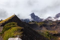 Facendo un'escursione nelle montagne circondate dalle nuvole fotografia stock
