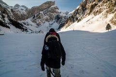 Facendo un'escursione sopra il lago congelato con il piccolo villaggio, montagne svizzere Immagini Stock Libere da Diritti