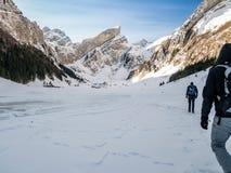 Facendo un'escursione sopra il lago congelato con il piccolo villaggio, montagne svizzere Fotografie Stock Libere da Diritti