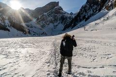Facendo un'escursione sopra il lago congelato con il piccolo villaggio, montagne svizzere Fotografia Stock Libera da Diritti