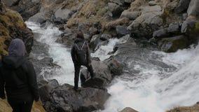 Facendo un'escursione vicino ad una torrente montano, provante ad attraversare archivi video