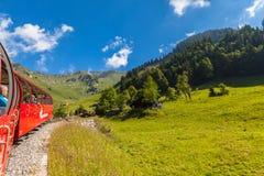 Facendo un giro turistico in treno a vapore in alpi svizzere Immagini Stock