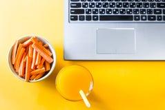 Facendo un spuntino con l'alimento sano al computer portatile immagini stock