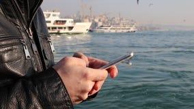 Facendo uso del app sullo smartphone nel seaview stock footage