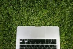 Facendo uso del computer portatile sul parco Fotografia Stock