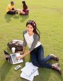 Facendo uso del computer portatile sulla città universitaria Immagini Stock