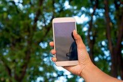 Facendo uso del telefono cellulare da prendere per possedere immagine Immagini Stock