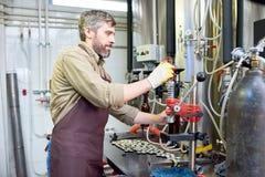 Facendo uso della capsulatrice della bottiglia alla fabbrica di birra Immagine Stock