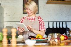 Facendo uso della compressa di Digital in cucina immagine stock