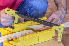 Facendo uso della sega della mano e del contenitore di mitra Fotografie Stock Libere da Diritti