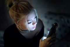 Facendo uso dello smartphone sul letto Fotografie Stock Libere da Diritti
