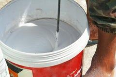 Facendo uso di attrezzatura fatta dalle polveri miste d'acciaio intonachi il gesso e l'acqua in secchio immagine stock libera da diritti