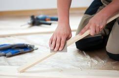 Facendo uso di carta vetrata per la lucidatura della plancia di legno Immagine Stock